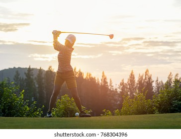 Asian woman golf player doing golf swing tee off on the green sunset evening time, she presumably does exercise.  Healthy and Lifestyle Concept