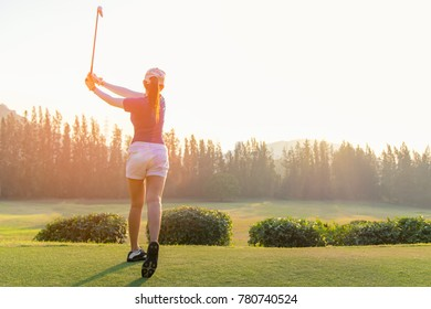 Asian woman golf player doing golf swing tee off on the green sunset evening time, she presumably does exercise.  Healthy and Lifestyle Concept.