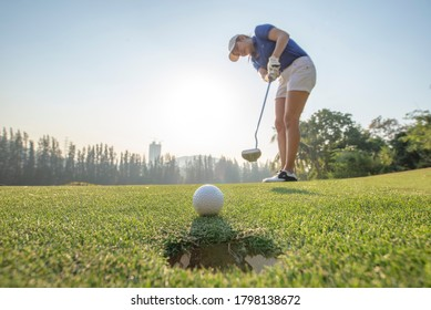Asian woman Golfer action to win after long putting golf ball on the green golf. morning time.