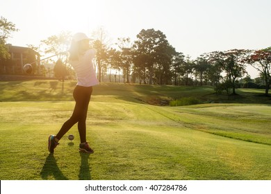 Asian woman golfer hit sweeping golf course in the summer.