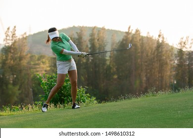 Asian woman golfer playing golf at golf course ,Golfer hitting golf ball , Healthy Holiday Concept