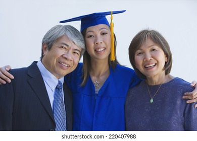 Asian woman in graduation cap and gown with parents