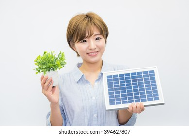 asian woman with green plant and solar panel