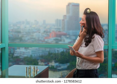 Asian woman in hair curlers getting ready for work doing  morning makeup routine putting makeup brushes near face with Lipsticks on table and Business buildings on background. Copy space