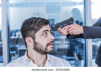 Asian Woman hand with black metal gun near business arabian man head Scary beard face look at muzzle of pistol barrel in office day light room space against city town background