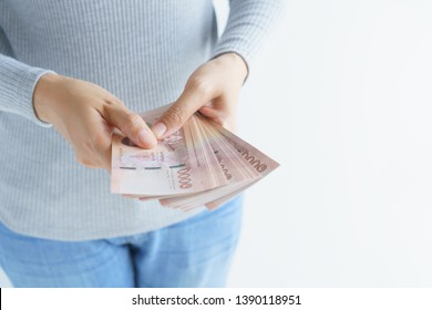 Asian woman hand counting money on white background. Money baht of thailand in her hand.