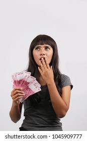 asian woman hand give Indonesian Money Rupiah. indonesian women thinking money rupiah for gift on white background