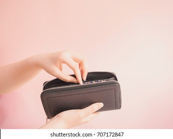 asian woman hand hold and insert money in her blue purse with pink pastel background