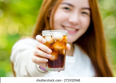 asian woman hand holding fresh coca cola with ice cubes