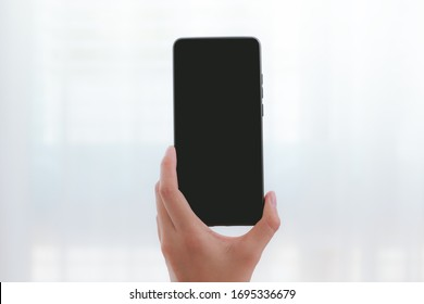 asian woman hand holding on blank black screen smartphone isolated on transparent curtain background