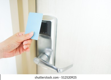 Asian woman hand holds card for door access control scanning key card to lock and unlock door. Security door open / close system concept. white background with copyspace