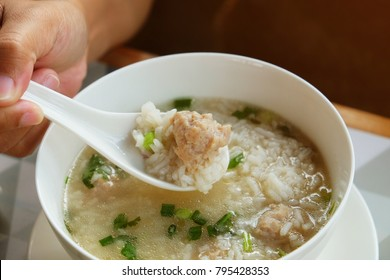 Asian woman hand using plastic white spoon to ladle porridge or rice congee mixed with pork meat for her breakfast