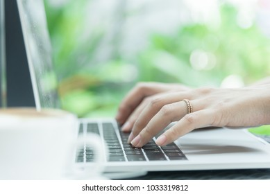 Asian woman hands and married ring has touching and typing on laptop computer with blurred coffee, computer and view outside window.