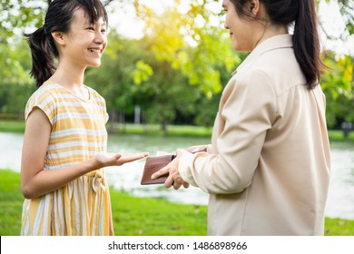 Asian woman hands open wallet,mother or guardian giving pocket money to daughter,smiling beautiful child girl demanding money, allowance,parent pulls out money from wallet to give her in outdoor park