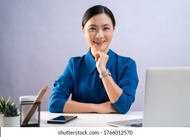 Asian woman happy smiling in blue shirt looking at camera, working on a laptop at office. isolated on white background.