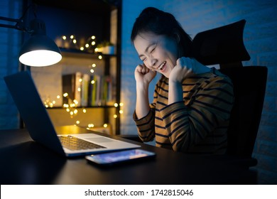 Asian woman happy smiling working on a laptop at the night at home and making winning gesture. WFH. Work from home avoid COVID 19 concept.