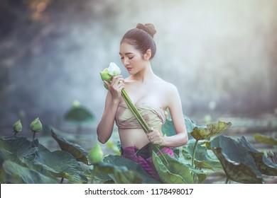 Asian woman harvest lotus flower in the garden, Thailand.