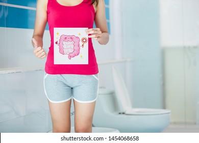 asian woman has a good intestine with cartoon billboard in wc