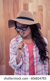 Asian woman with hat holding pencil against wooden wall
