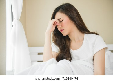 Asian woman have a headache in bedroom morning because sleep problem
