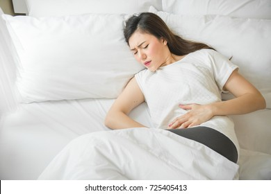 Asian woman have a stomachache in bedroom because menstruation