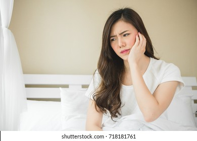 Asian woman have a toothache on white bed in white bedroom in morning