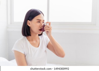 Asian Woman having asthma using the asthma inhaler for being healthy on her bed in bedroom