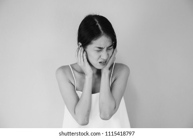 Asian woman having earache or ear pain in black and white tone