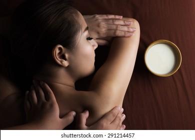 Asian woman having massage and bowl of milk , spa salon Beauty treatment