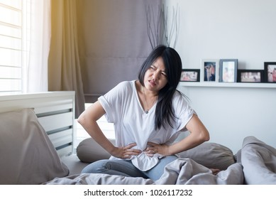 Asian woman having painful stomachache on bed,Menstrual period