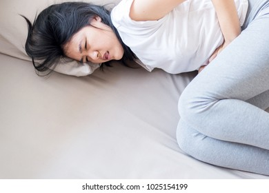 Asian woman having painful stomachache,Female suffering from abdominal pain,Period cramps or premenstral syndrome at home,Copy space