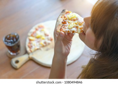 Asian woman having tasty pizza and soft drink in restaurant. Young girl eating a piece of delicious pizza. Happy female enjoy eating Italian fast food.