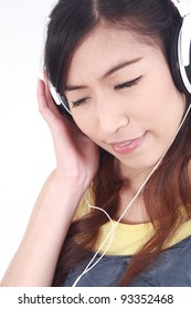 Asian Woman with headphones listening to music - isolated over a white background