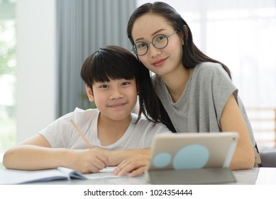 Asian woman helping asian boy doing homework on table at home.