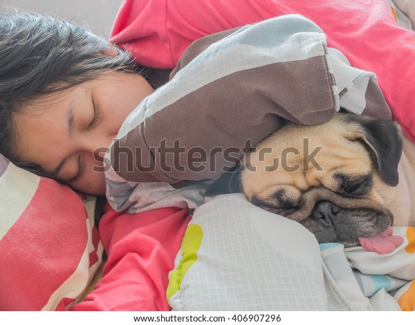 Asian Woman and her cute puppy pug dog sleep in the bed