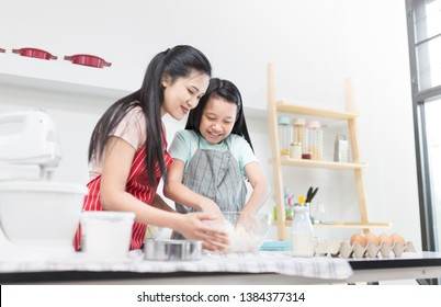 asian woman and her daughter cooking homemade bakery in kitchen room, they feeling fun and happy, sifting flour learning activity, close up children