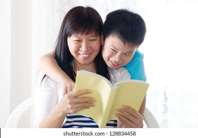 Asian woman and her son sharing a book