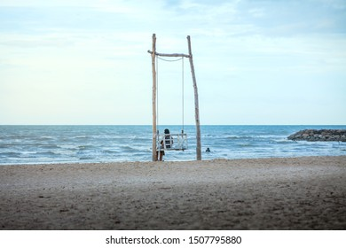 Asian woman and her son sitting on the white old wooden swing chair looking the couple swimming on the tropical beach during sunrise morning, holidays vacation outdoors at paradise island in Thailand.