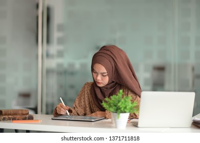 Asian woman in hijab using tablet and laptop in office