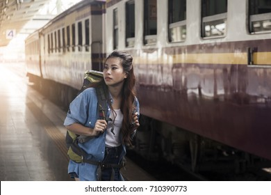 Asian woman hipster backpacker walking and finding timetable for travel by train at platform of railway station.