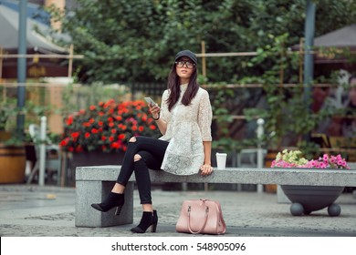 Asian woman or hipster student with smartphone and coffee sitting on bench on the city street with trees and flowers. Mixed race Asian Chinese Caucasian elegant beautiful female model.