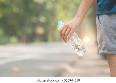 Asian woman hitchhiker hand holding bottle of water on nature background. copy space. Traveler.