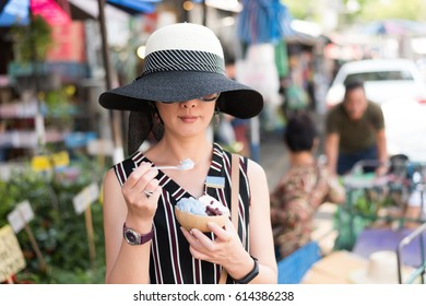 asian woman hold a coconut ice at Chatuchak weekend market, Bangkok, Thailand