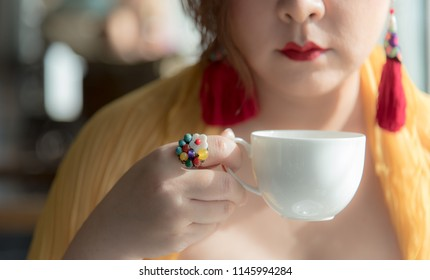 Asian woman hold a cup of fresh brew tea or coffee during afternoon tea or high tea against herself wearing red lips with colorful fancy earring and ring. Elegant oriental setting. Natural lighting.
