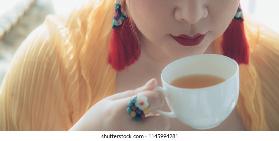 Asian woman hold a cup, smile to sip fresh brew tea during afternoon tea or high tea against herself wearing red lips with colorful fancy earring and ring. Elegant oriental setting. Natural lighting.