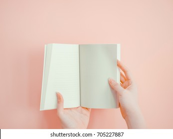 asian woman hold and open blank page of book by both hand with pink pastel background