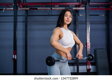 asian woman holding barbell.  asian woman using barbells in gym.