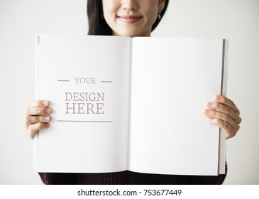 An Asian woman is holding a blank magazine