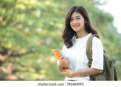 Asian Woman holding book with attractive smiling at park. Woman with education concept.