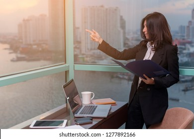 Asian woman holding folder of documents, pointing up on copy space and standing in front of windows in an office building overlooking the city and river.